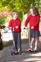 pojke och flicka som rider på skoter på väg till skolan foto