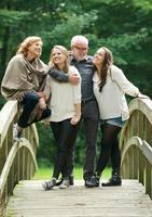 lycklig familj som står tillsammans på en bro i skogen foto