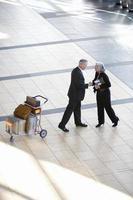 affärsman och kvinna som skakar hand nära bagage vagn i airp