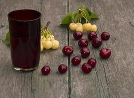 glas juice och bär på ett träbord foto