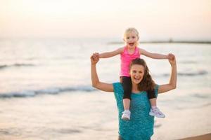 glad mamma som håller dotter på stranden vid solnedgången foto