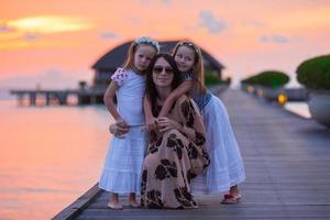 ung mamma och två hennes barn på en exotisk utväg foto