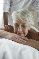 äldre kvinna som har massage foto
