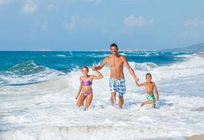 far och barn som leker på stranden