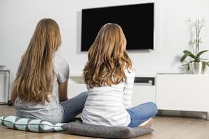 bakifrån av syskon som tittar på tv hemma foto