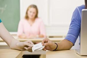 elever passerar anteckningar i klassrummet foto