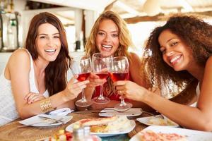 grupp kvinnliga vänner som tycker om måltid i utomhusrestaurangen