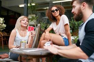 grupp ungdomar som spelar kort på caféet foto