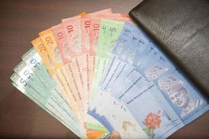 sedlar med malaysia pengar med brun plånbok foto