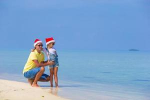 liten flicka och lycklig pappa i santa hatt på stranden foto