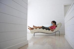 pojke med far som ligger på loungestol foto