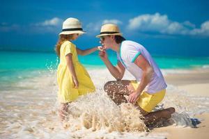 lycklig far med sin lilla dotter som tycker om strandsemester foto