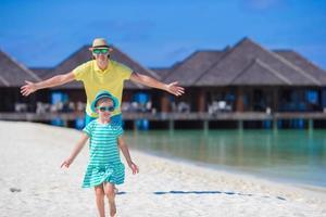 ung far och liten dotter på den tropiska stranden