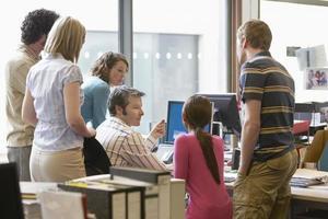 multietniska chefer runt kollega som använder dator foto