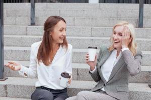 vackra unga kvinnliga kollegor kommunicerar med glädje foto
