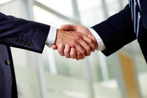 två lämpliga affärsmän som skakar hand hårt