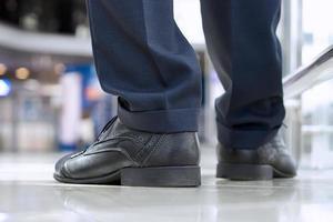 närbild av affärsmans fötter i skor på golvet foto
