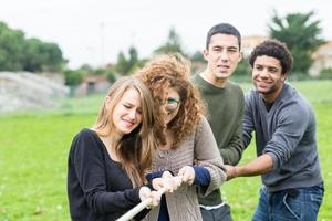 multiraciala människor som spelar dragkamp foto