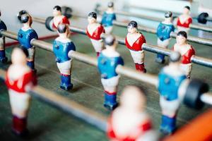 närbild av ett bordfotbollsmatch i röda och blå tröjor foto
