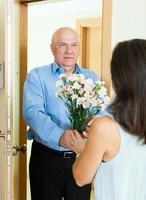 mogen man ger en massa blommor till kvinnan foto