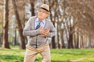 senior som har ett hjärtstillestånd i parken foto