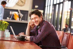 man som arbetar på dator på kafé, porträtt foto
