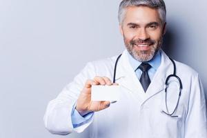 läkare håller visitkort.