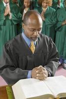 predikant och kör som ber i kyrkan foto