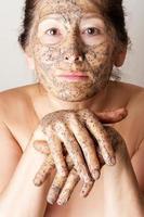 mogen kvinna som gör kosmetisk mask foto