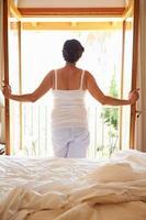 bakifrån av kvinnan som vaknar upp i sängen på morgonen foto
