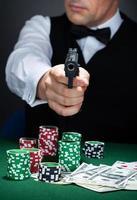 porträtt av en croupier som siktar med en pistol foto