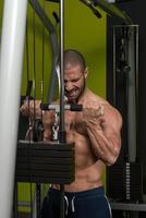 muskulös man gör övning med tung vikt för biceps foto