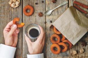 man håller glas kaffe och pumpa munk. foto