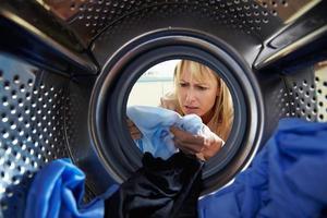 kvinna av misstag färgning tvätt inuti tvättmaskin foto