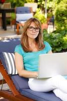 modern mogen kvinnastående med bärbar dator foto