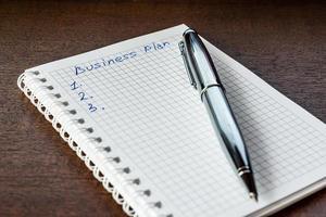 utarbeta affärsplanen, skriv i anteckningsboken foto