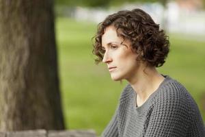 mogen kvinna som tänker i parken foto