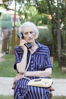 äldre kvinna pratar i telefon i trädgården foto