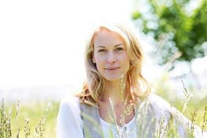 mogen blond kvinna som sitter i ängen på solig dag foto