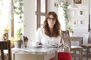 vacker kvinna sitter vid skrivbordet i kafé foto