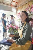 blomsterhandlare som arbetar i blomsterbutik foto