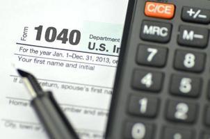 närbild av oss skatteformulär, penna och miniräknare foto