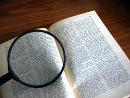 bok och förstoringsglas foto