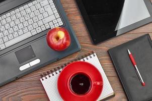 bärbar dator och kontorsmaterial på träbord foto