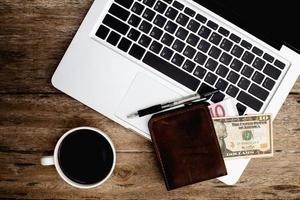 kaffe och bärbar dator på gamla träbord. foto