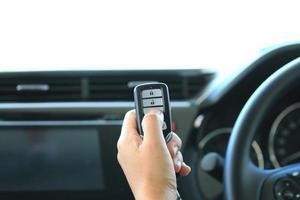 kvinna hand håller en fjärrnyckel bil och tryck foto