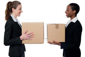 unga affärskvinnor som håller små lådor foto
