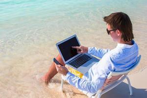 ung affärsman som använder bärbar dator och telefon på den tropiska stranden foto
