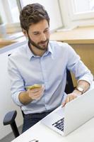 avslappnad affärsman som betalar online med kreditkort. e-handel foto