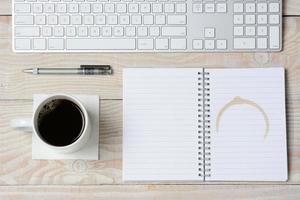 vitt skrivbord med kaffe och tangentbord foto